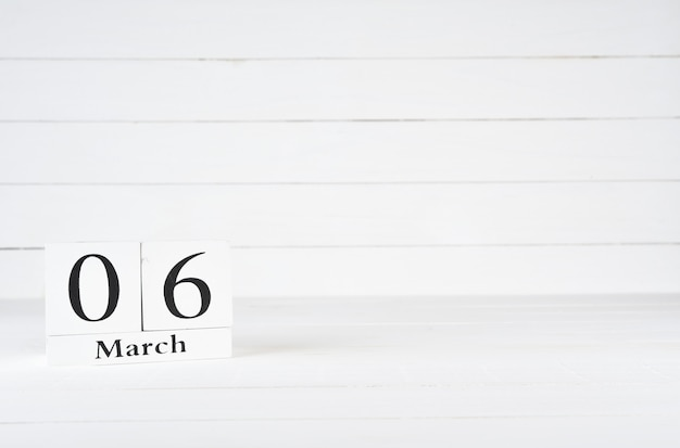 March 6th, day 6 of month, birthday, anniversary, wooden block calendar on white wooden background with copy space for text.