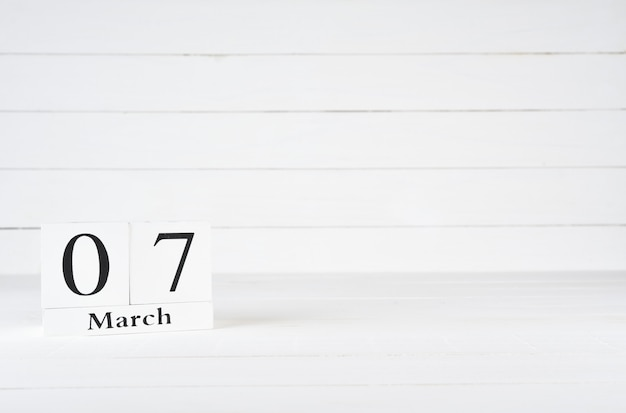 March 7th, day 7 of month, birthday, anniversary, wooden block calendar on white wooden background with copy space for text.