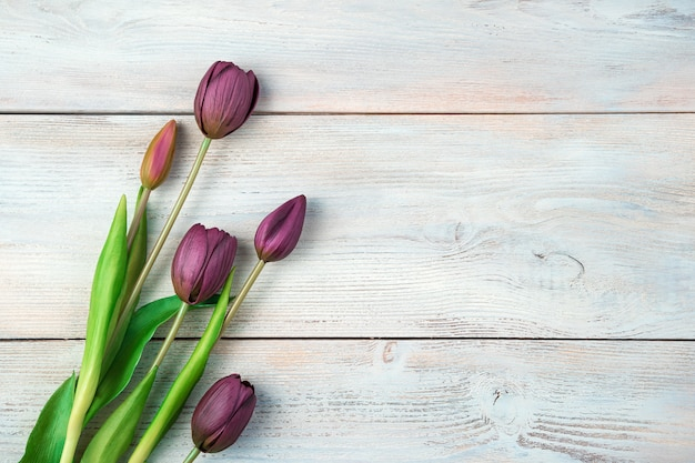 March 8, festive background with tulips on a light wooden background.