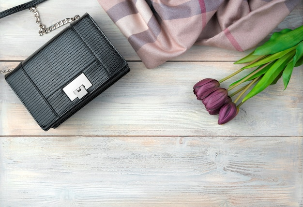 March 8, holiday background with flowers, bag, scarf wooden background.