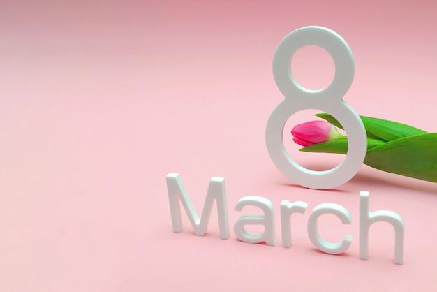 3月8日国際女性の日。ピンクのユニフォームの背景に対してチューリップの背景に対して8番、テキストの場所。広告、はがき、おめでとうございます。