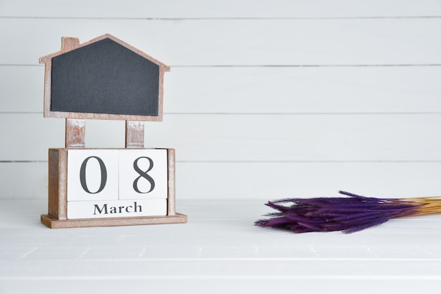 8 марта текст деревянный блок календарь с фиолетовым высушенный цветок на белом фоне деревянные.