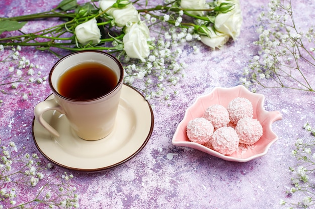 March 8 women's day card with white flowers,sweets and a cup of tea .