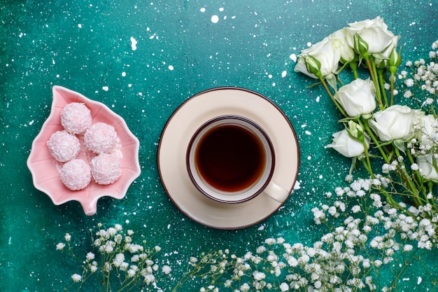 March 8 women's day card with white flowers,sweets and a cup of tea Free Photo