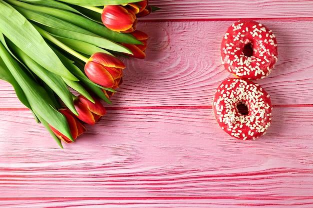 3月8日、女性の日、ピンクの表面にピンクのドーナツ、上面図、チューリップの花束