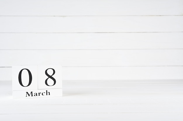 March 8th, day 8 of month, birthday, anniversary, wooden block calendar on white wooden background with copy space for text.