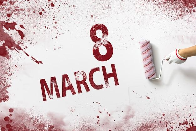 3月8日。月の8日目、カレンダーの日付。手は赤いペンキでローラーを保持し、白い背景にカレンダーの日付を書き込みます。春の月、年の日の概念。