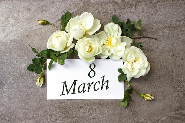3月8日。月の8日目、カレンダーの日付。白いバラは、カレンダーの日付とパステルグレーの背景に国境を接します。春の月、年の日の概念。
