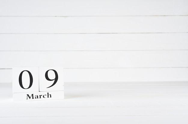 March 9th, day 9 of month, birthday, anniversary, wooden block calendar on white wooden background with copy space for text.