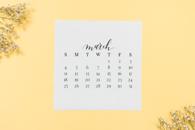 March calendar with flower branches on table