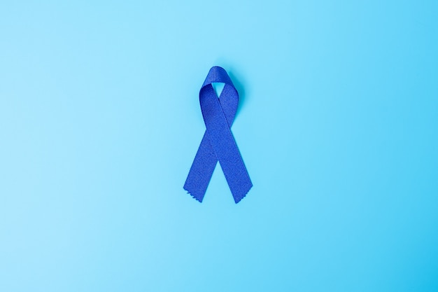 March colorectal cancer awareness month, dark blue color ribbon for supporting people living and illness. healthcare, hope and world cancer day concept
