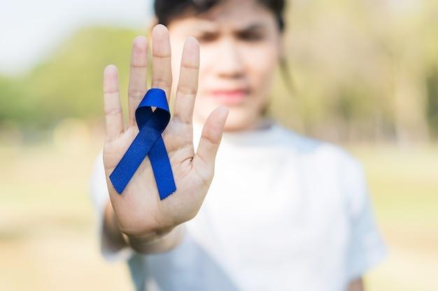 3月の結腸直腸がん啓発月間、紺色のリボンを持った女性