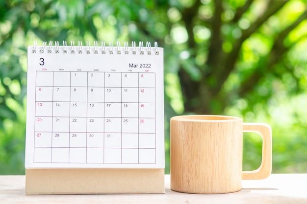 3월 달, 주최자를 위한 캘린더 데스크 2022는 녹색 자연 배경을 가진 나무 테이블에 대한 계획 및 알림을 제공합니다.