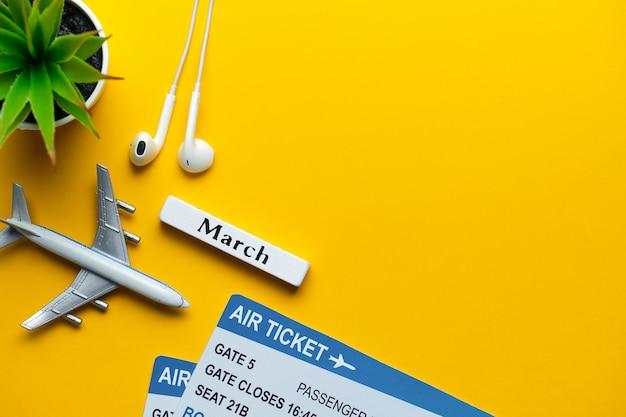 3月の休暇のコンセプト-黄色の壁のチケットとおもちゃの飛行機。コピースペース