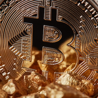 Marco shot of golden bitcoin coin and mound of gold. bitcoin as desirable as digital gold concept or concept of financing bitcoin cryptocurrency in noble metal