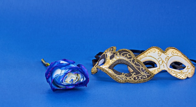 Mardi gras carnival masquerade mask on blue background with copy space