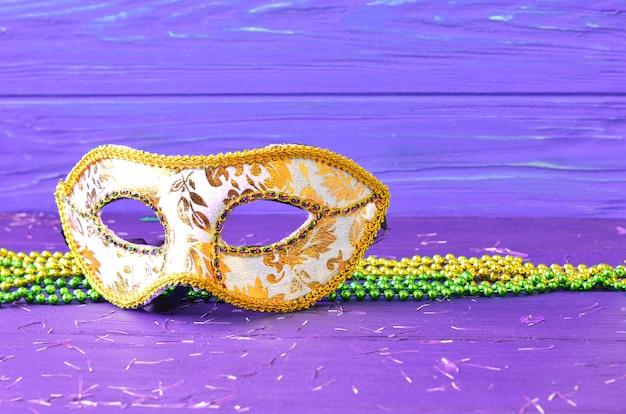 木製の背景にマルディグラのマスクとビーズ。マディグラのカーニバルアクセサリー