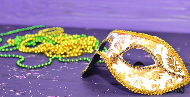 마디 그라 마스크와 구슬 나무 테이블에. 마디 그라 카니발 액세서리, 색종이 조각, 축제, 베네치아 또는 카니발 마스크. 가장 무도회 축하 개념.