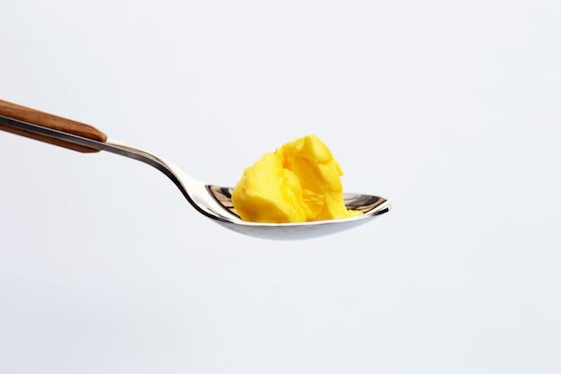 白い表面にスプーンでマーガリンチーズバター