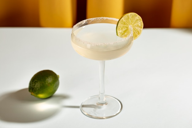 Margarita cocktail in saucer glass with lime on white table