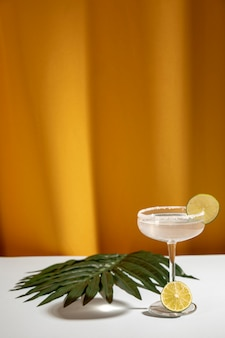 Margarita cocktail with sliced limes and palm leaf on white table near yellow curtain