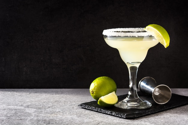 Margarita cocktails with lime in glass on gray