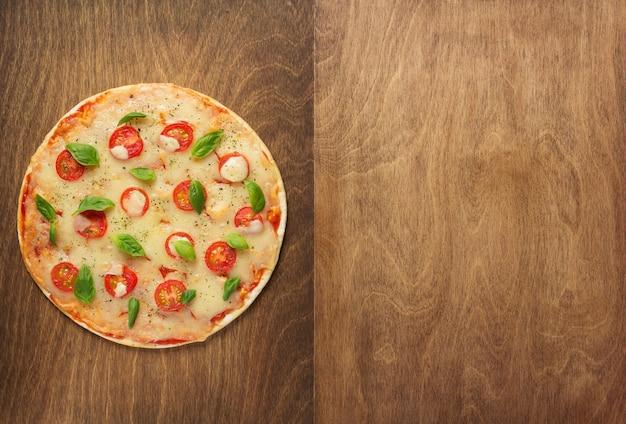木製のテーブルでマルゲリータピザ、上面図