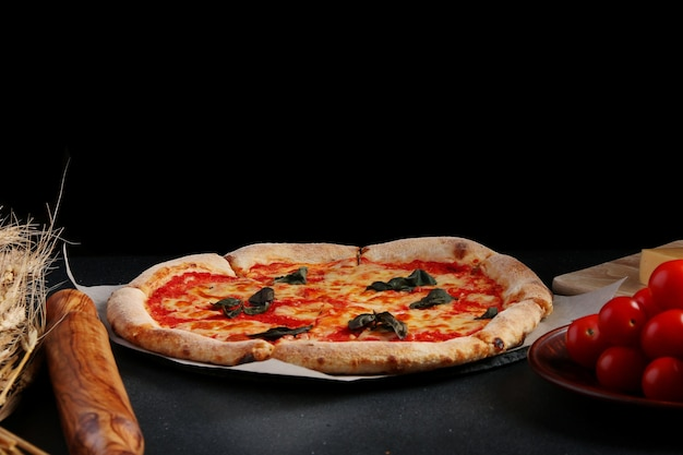Margarita pizza and tomato cherries on dark background