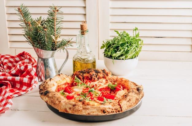 白い木製に新鮮なルッコラとクリスマスの装飾が施されたマルゲリータピザ