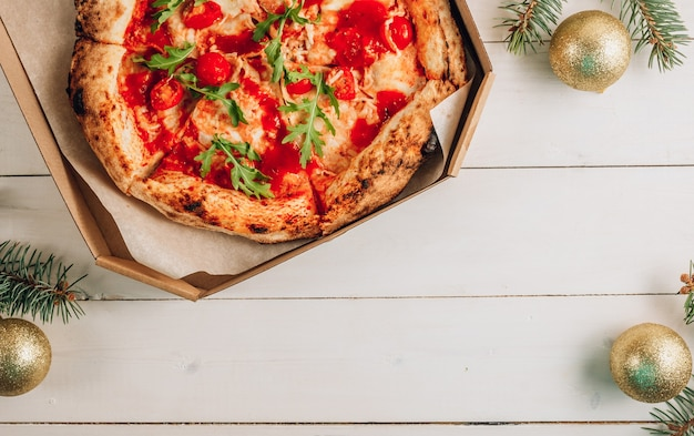 Margherita pizza with fresh arugula and christmas decorations on white wooden.