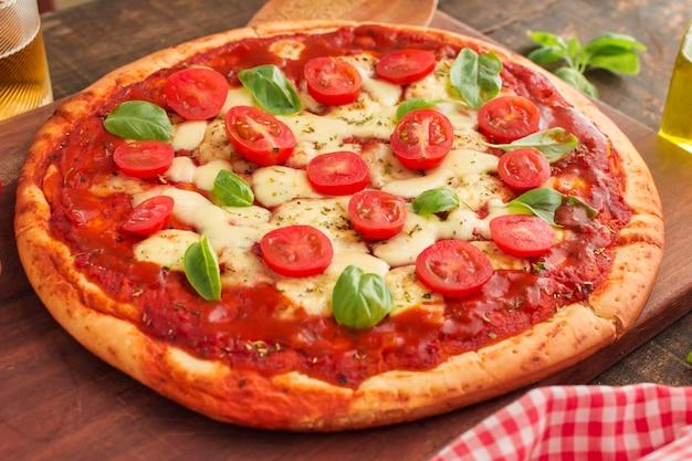 Большая пицца margherita на деревянной разделочной доске