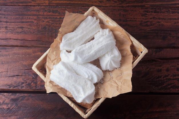 マリアモールは、素朴な木製のテーブルの上に砂糖、卵白、無色のゼラチン、すりおろしたココナッツで作られた典型的なブラジルのスイーツです