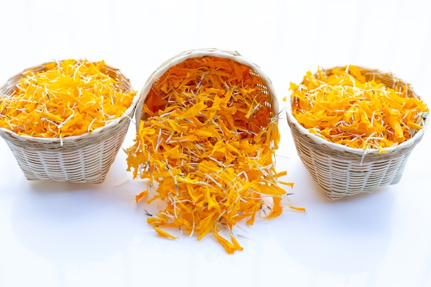 Marigold flower petals in bamboo basket on white.