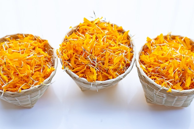 Marigold flower petals in bamboo basket on white
