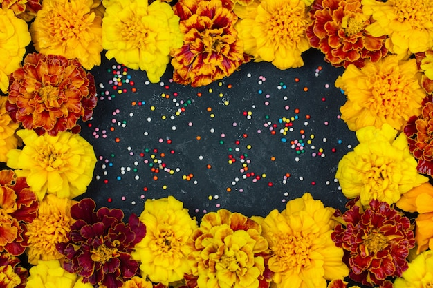 Marigold flowers are red yellow and orange, on a dark background a frame for halloween and dia de los muertos is a musical celebration