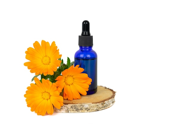 Marigold flowers and dropper bottle on birch wood slice and yellow background. copy space.