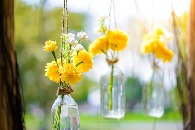 The marigold flowers in a glass bottle hanging