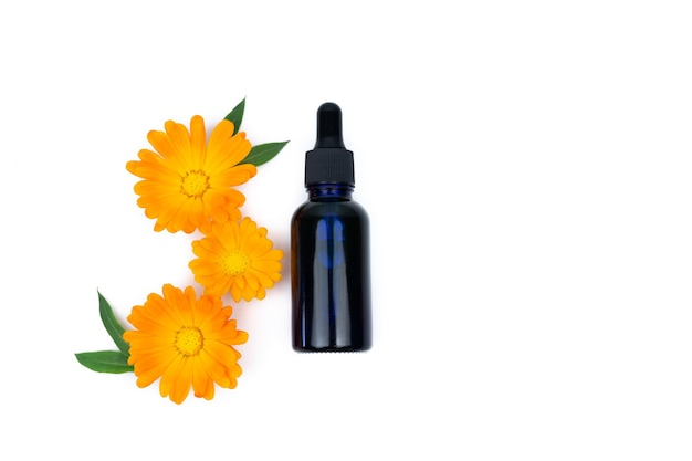 Marigold flowers with leaves and dropper bottle on yellow surface. copy space. top view.