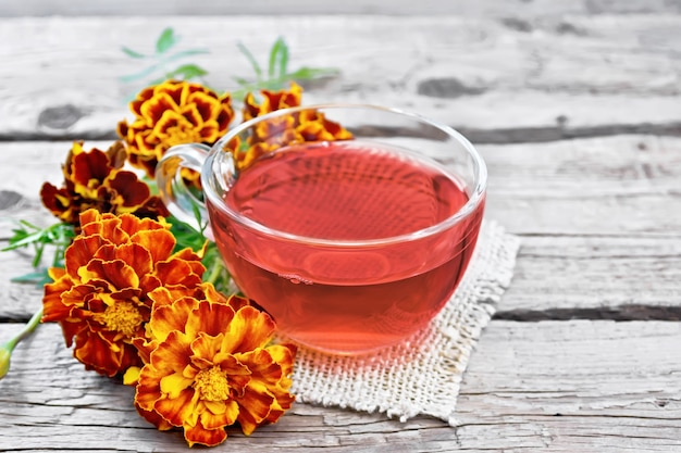 Marigold herbal tea in a glass cup, fresh flowers on a napkin of burlap on of an old wooden board