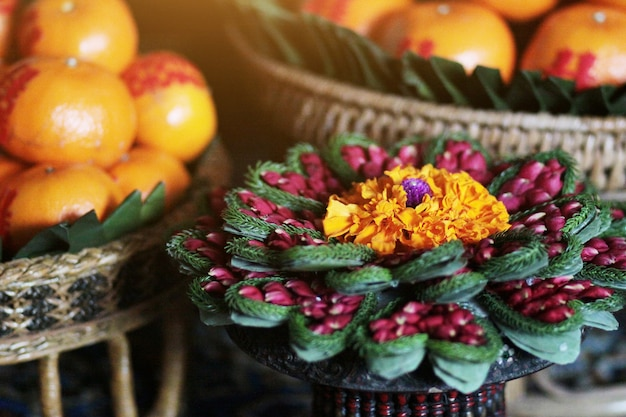 Marigold and rose flowers in vase made of banana leaf in traditional thai art
