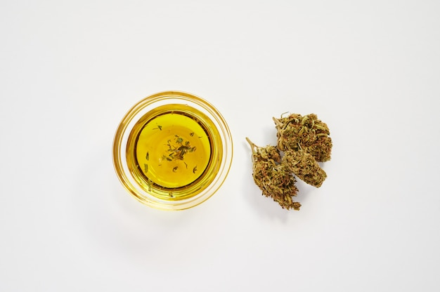 Marijuana buds and a small bowl of cbd oil on a white background