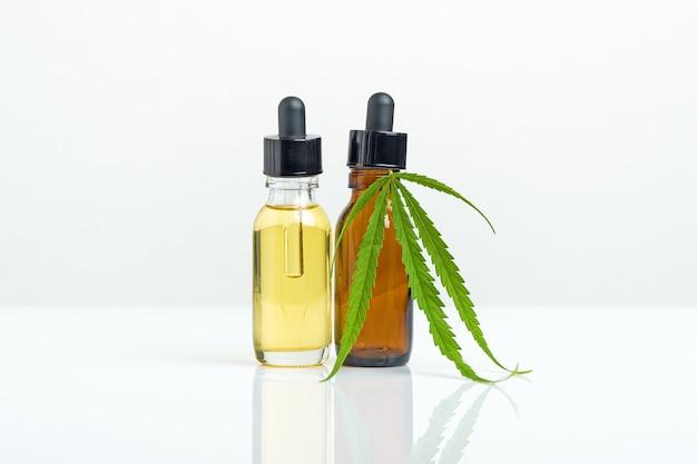 Марихуана. масляные экстракты каннабиса cbd в банках с травами на белом фоне. концепция медицинской марихуаны.