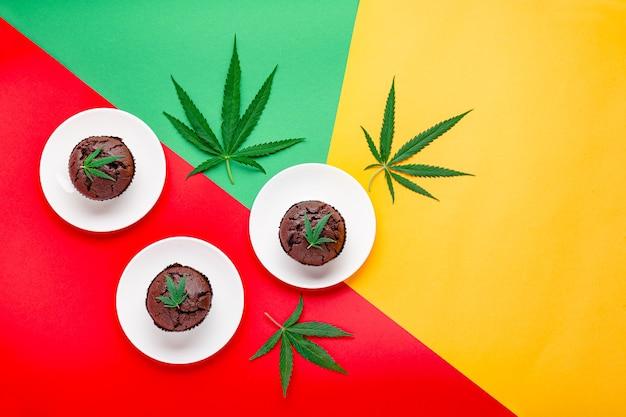 雑草cbdとマリファナチョコレートカップケーキマフィン。食品デザートに含まれる医療用マリファナ麻薬。大麻と大麻の葉の雑草マフィンはラスタマンの旗の背景に提供されます上面図スペースをコピーします。