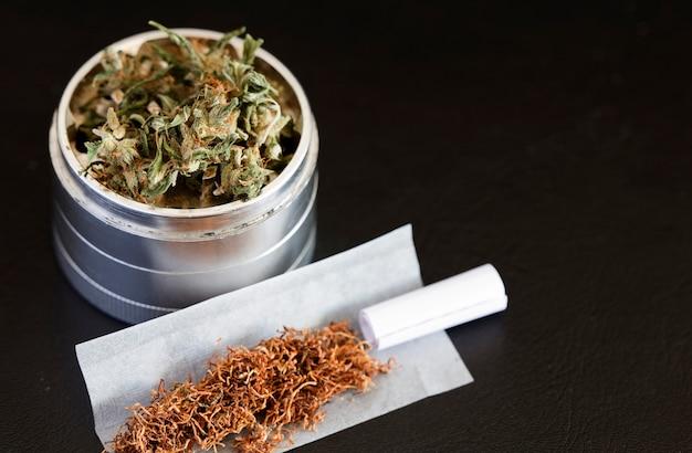 Marijuana on grinder with cigar dark background