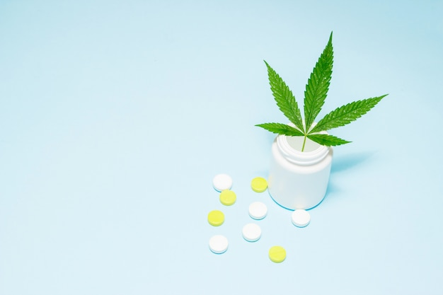 Marijuana leaf in medical pills bottle on blue.