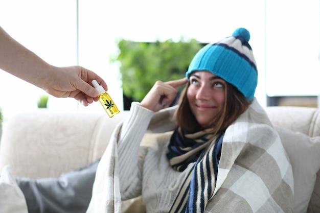 帽子と毛布の下のスカーフで病気の女性と手のクローズアップのマリファナオイル