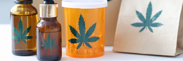 Marijuana pills and bottles with extract standing on background of gift sale of narcotic drugs