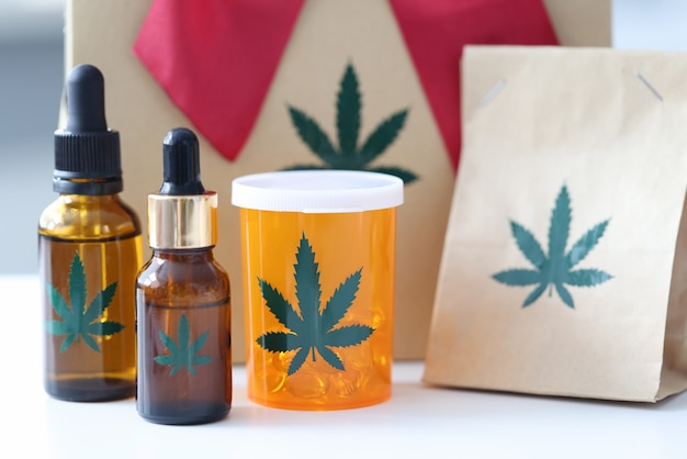 Marijuana pills and bottles with extract standing on background of gift