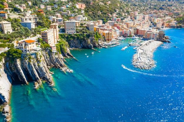 灯台があるマリーナと防波堤。イタリア、ポルトフィーノに近いカモーリのリグリア海の港へのセーリングボート。伝統的なイタリアのカラフルな家の空撮