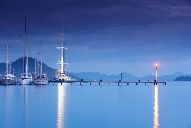 Marina at night with moored yachts
